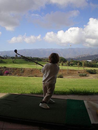 Un niño pega bolas en una cancha de prácticas.