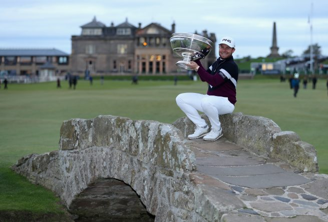 Tyrrell Hatton of England celebrates victory with the trophy on the Swilken Bridge following the final round of the 2017 Alfred Dunhill Championship at The Old Course on October 8, 2017 in St Andrews, Scotland. (Photo by Richard Heathcote/Getty Images)
