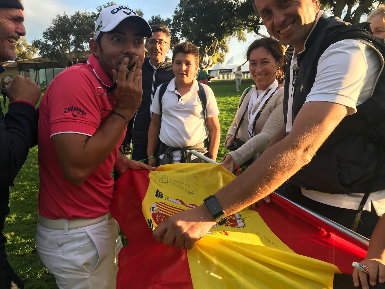 Pablo Larrazábal firma una bandera de España a unos aficionados en Valderrama. © Tengolf