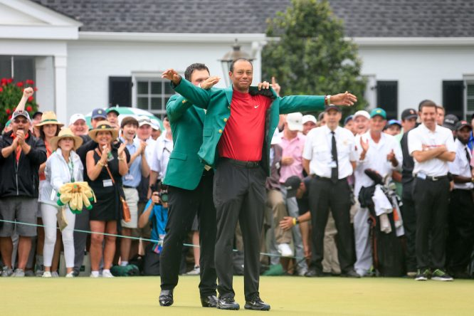 Tiger Woods recibe la Chaqueta Verde de su predecesor, Patrick Reed. © Golffile | Fran Caffrey