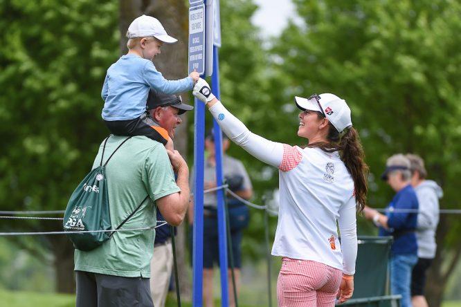 Nuria Iturrios choca la mano de un joven espectador en el tee del 3 de Hazeltine durante la segunda ronda. (© Golffile | Ken Murray)